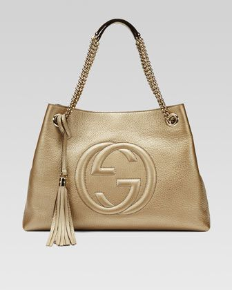 """Gucci Soho tote in metallic leather. Light fine golden hardware. Embossed interlocking G. Detachable leather tassel. Double chain shoulder straps with leather shoulder pad; 6"""" drop. Inside hook closur"""
