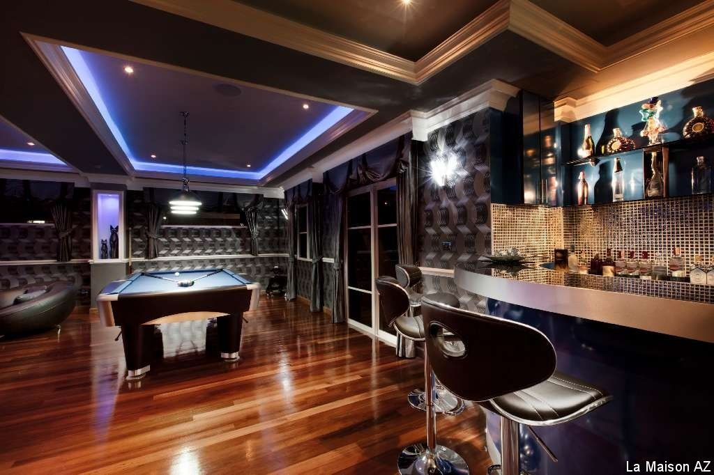 A modern man cave design with hardwood flooring, contemporary bar ...