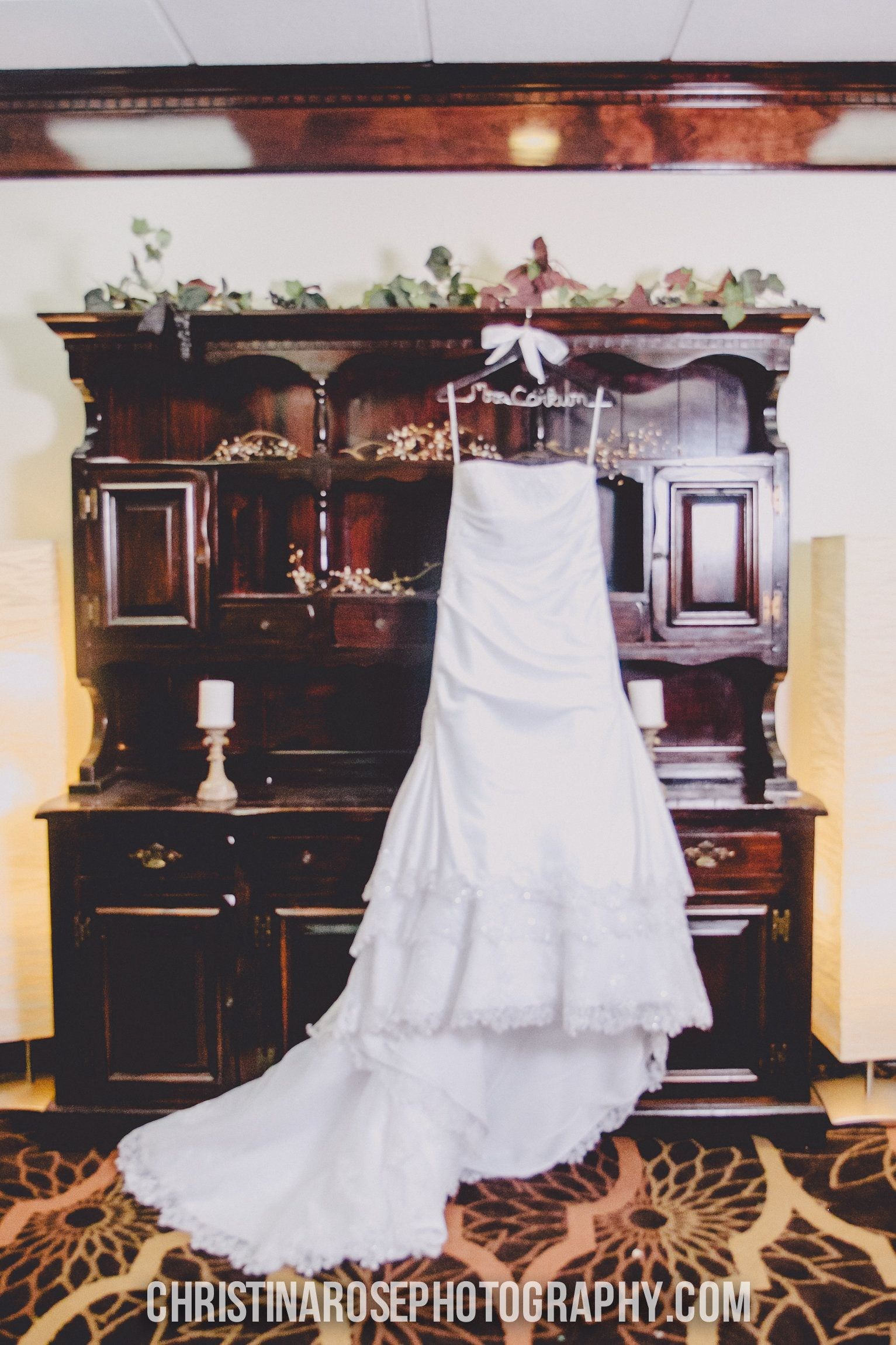 A white wedding gown hung on a personalized hanger in our Bridal Suite