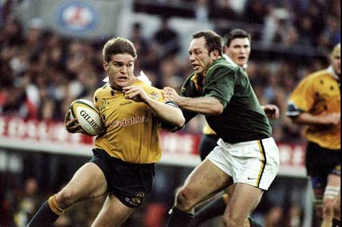 Tim Horan is tackled by Brendan Venter