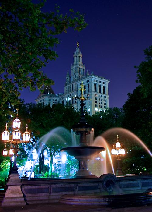 Farolas de gas rodeando la Fuente del City Hall Park, y al fondo el Manhattan Municipal Building