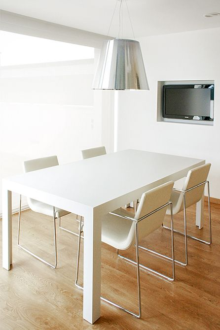 Chiralt Arquitectos I Comedor en vivienda moderna con mobiliario minimalista y suelo de parquet.