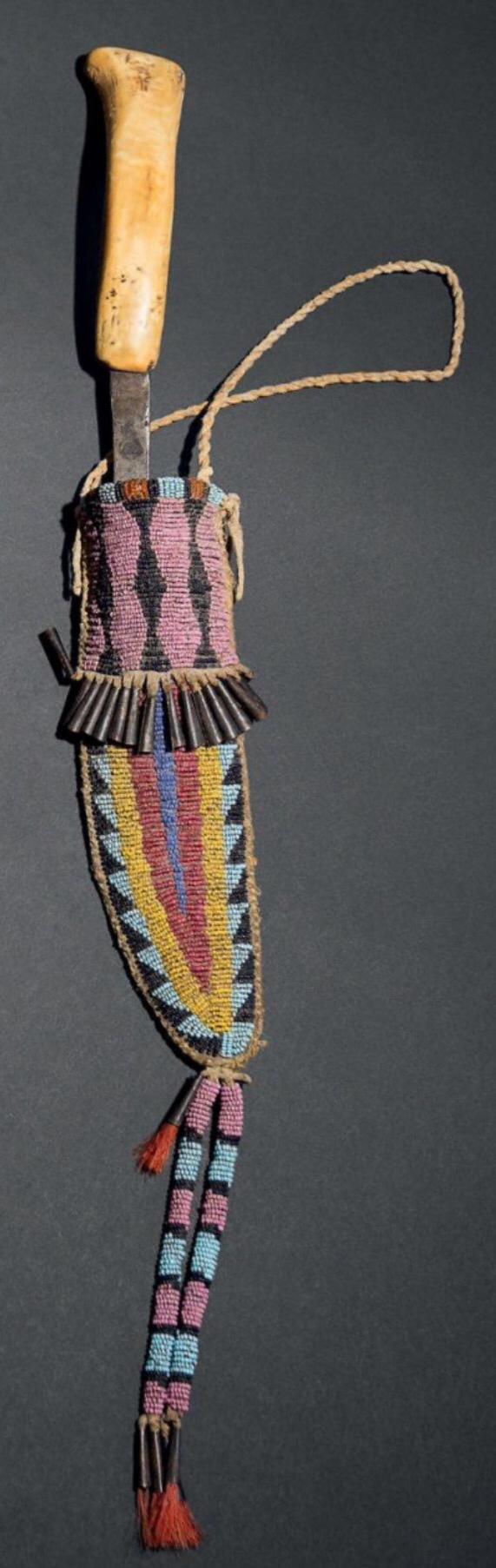 Нож и ножны, Кроу. Период 1880.  Кожа, бисер - ленивый стежок, железо, конский волос, окрашенный красным, конусы. Длина: 42,5 см. Из Коллекции Mario Luraschi. Короткий ремешок, позволяющий носить его на поясе. Нож состоит из длинного лезвия с ручкой из кости, форма лезвия может быть заимствована у древних лезвий из камня. Binoche et giquello. Декабрь 2013.