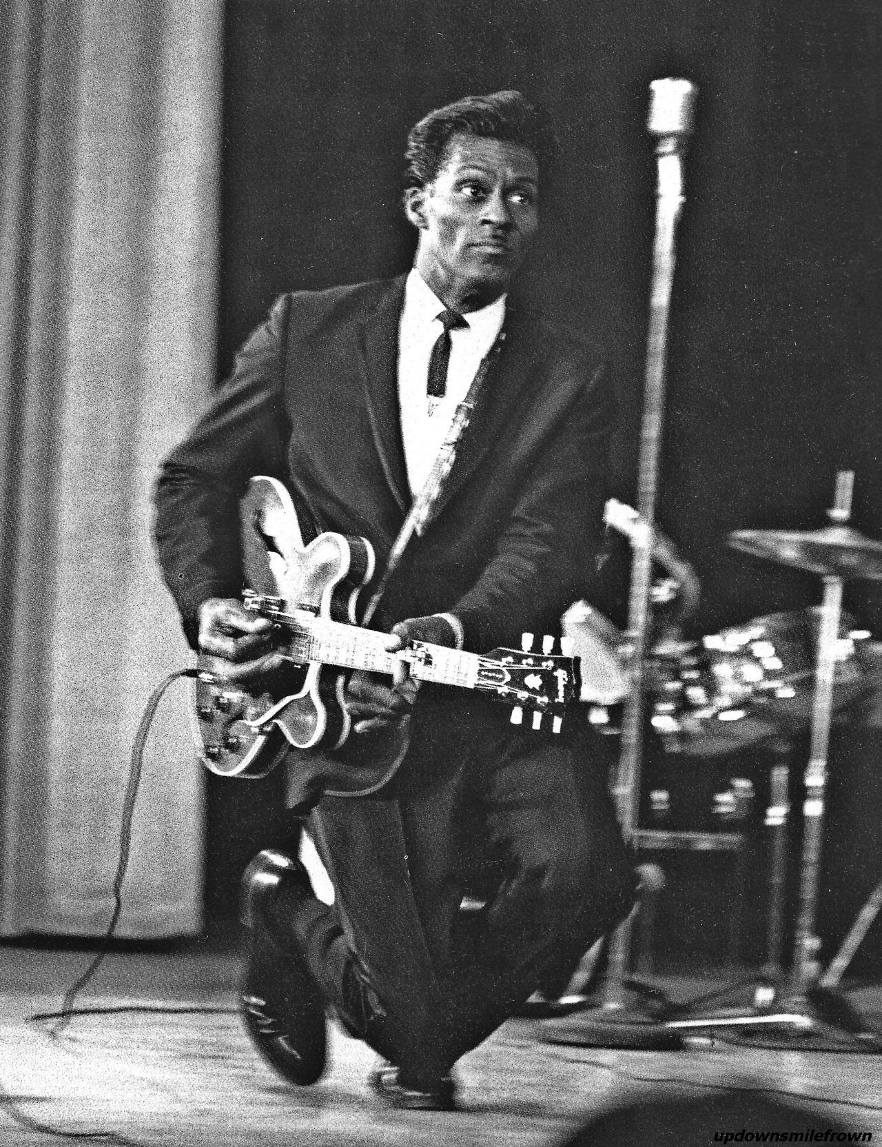 """Chuck Berry doing his trademark """"duck walk"""" move while playing. 