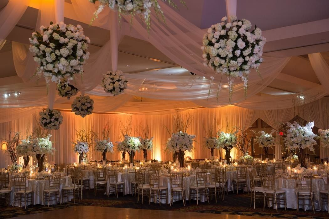 Tables set with tall white arrangements ,amber lighting