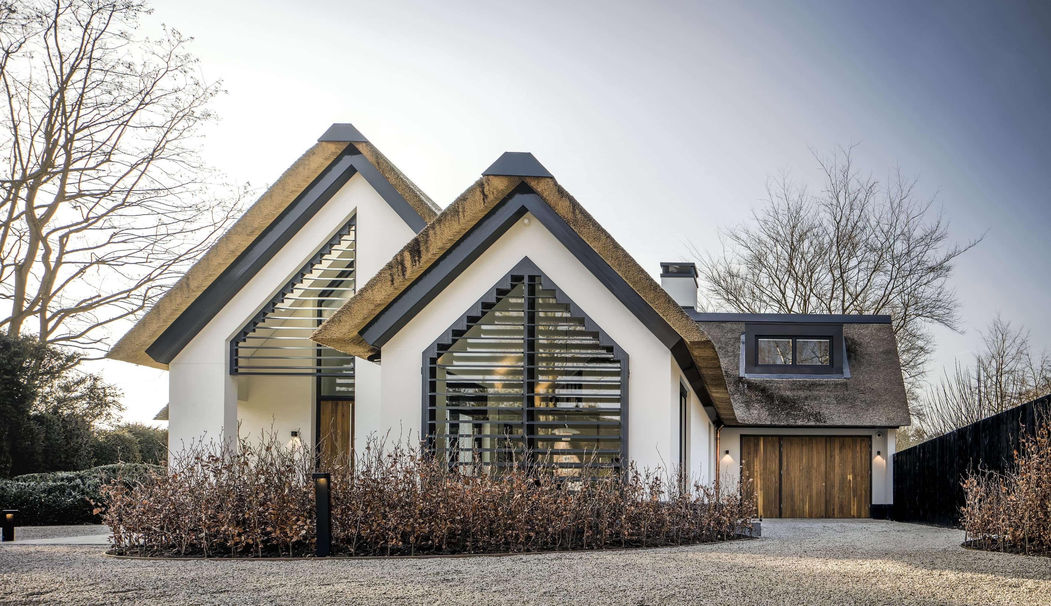 Witte villa met rieten dak donkere dakkapel louvre facade