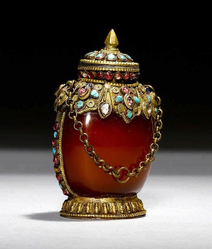 A RED-BROWN AGATE SNUFF BOTTLE IN A METAL MOUNT INLAID WITH TURQUOISES AND OTHER STONES IN A MONGOLIAN STYLE. China, height 9 cm. Matching stopper.