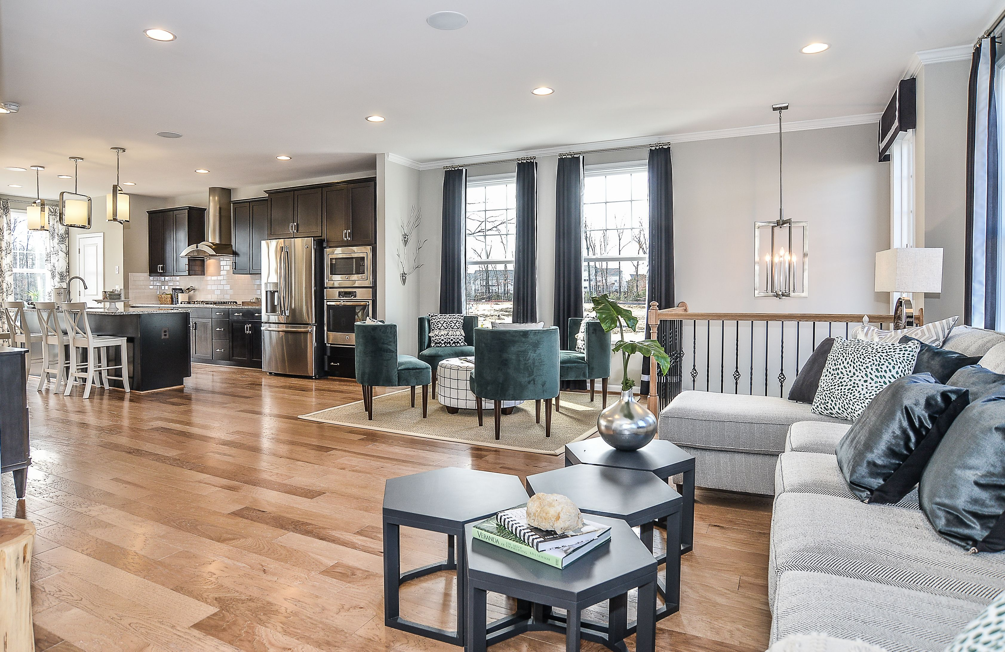 Light Hardwood Flooring Flows From The Great Room Through Beautiful Eat In Kitchen Inside Van Metre Homes Barnsley Townhome Model At Eastview Village