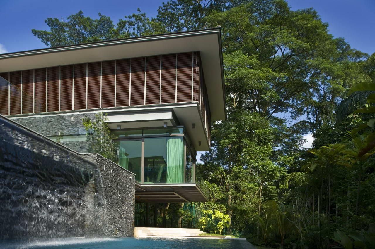Stunning tropical contemporary house design in the forest with waterfall above swimming pool also wide glass