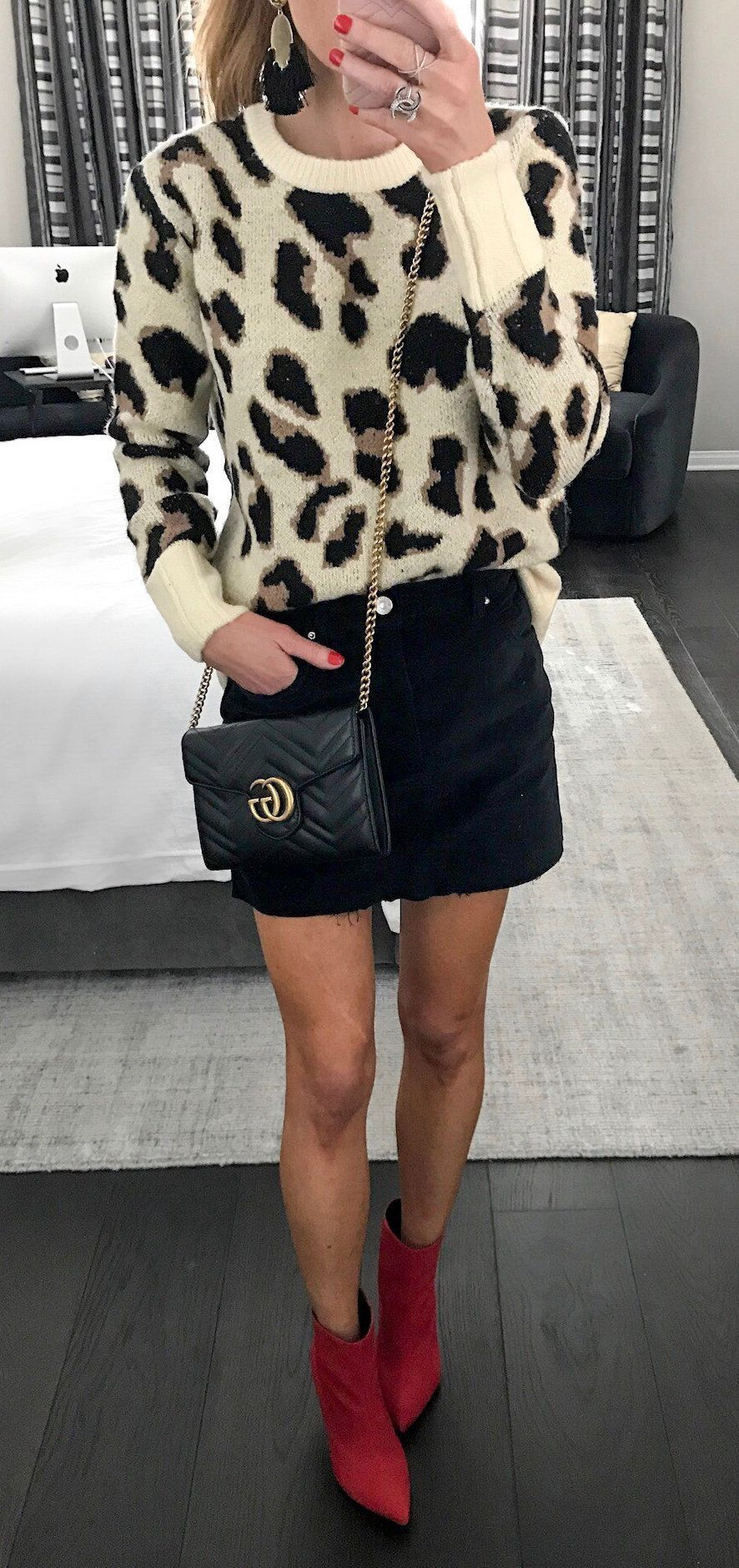 Animal print sweater with black mini skirt and red boots.
