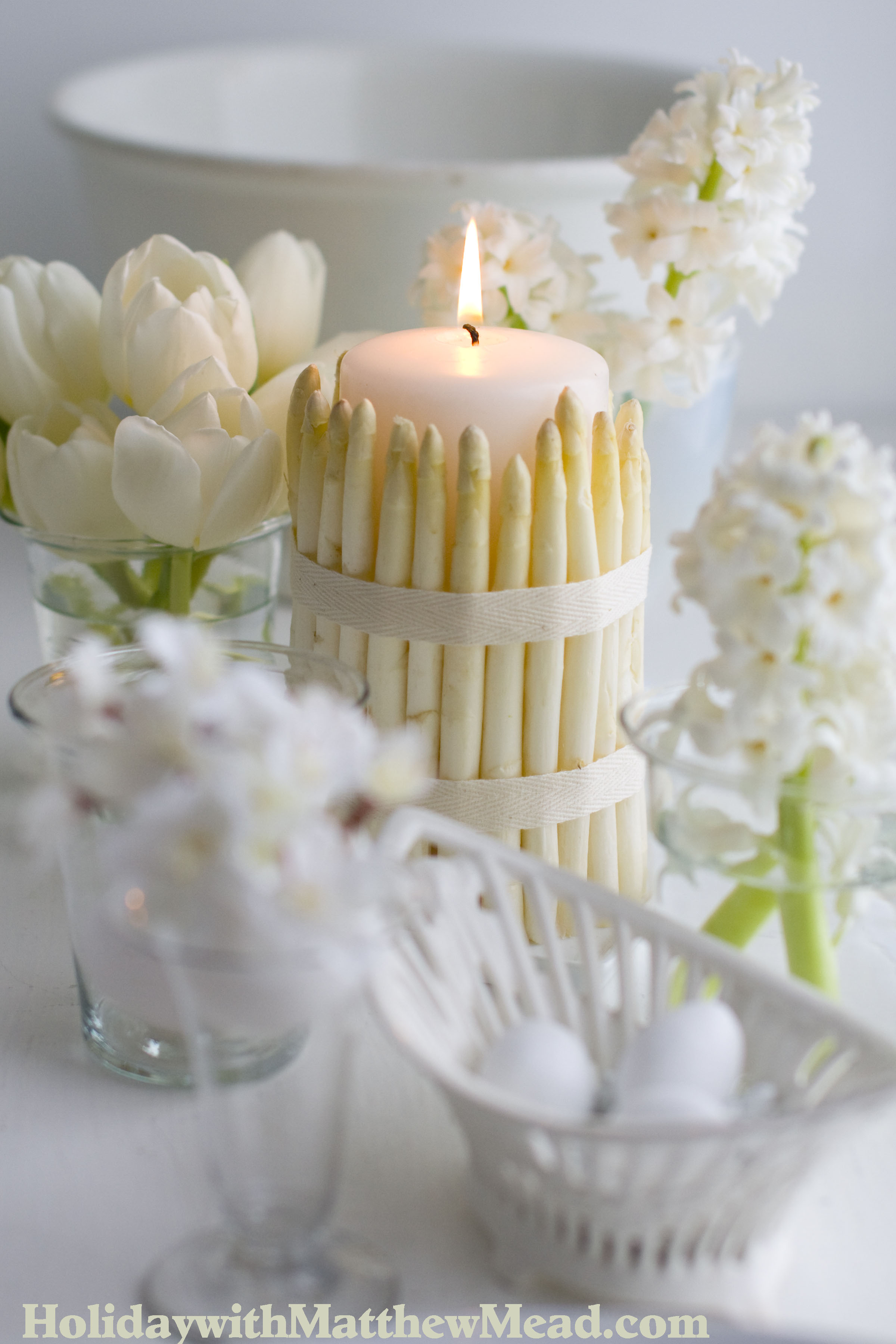 Surround a pillar candle with white asparagus and tie with a ribbon. Surround with assortment of vases with white flowers to make a beautiful dinner table. www.HolidaywithMatthewMead.com