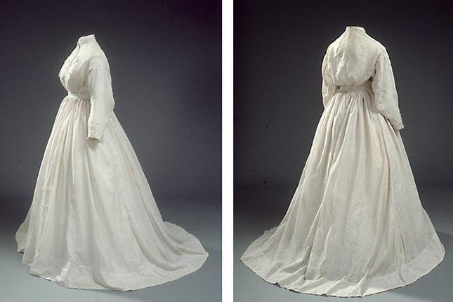 Lang kjole i hvidt stof med lille, rødt stjernemønster. Kjolen har lange ærmer og et lille slæb.