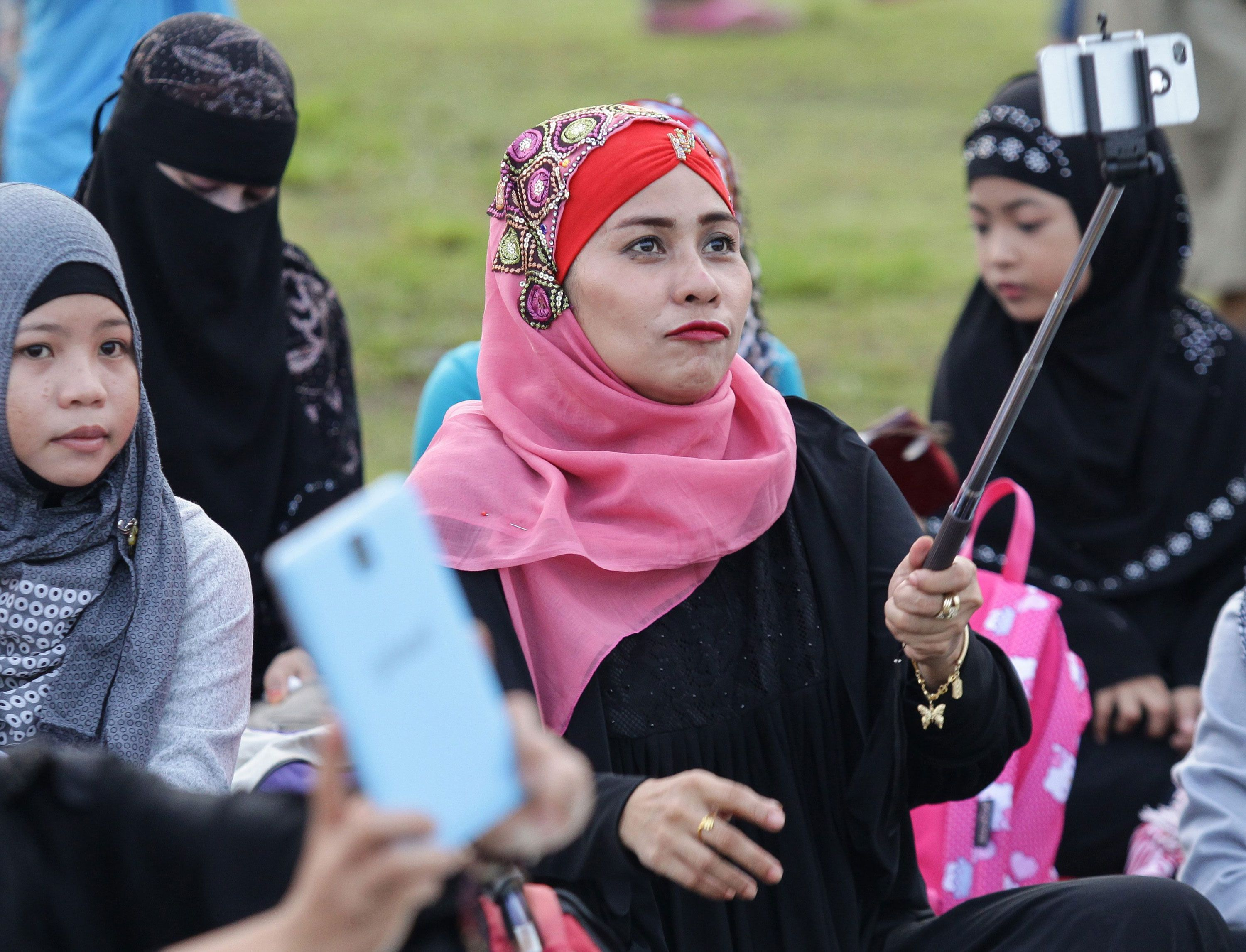 Filipino Muslim Women in Hijab and Veil takes a selfie as she attends morning prayers to celebrate Eid al-Adha at Luneta Park in Manila, the Philippines. [Mark R. Cristino/EPA]