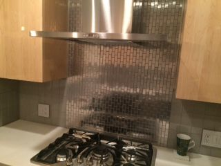 Stainless Steel Backsplash Behind The Stove And Smoke Glass Tile