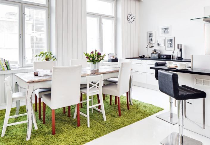 Avokeittiössä voi seurustella vieraiden kanssa ruoanlaiton lomassa. Korkeakiiltoiset kaapistot ja mustat baarituolit ovat HTH-keittiöiden mallistosta. Suuri vihreä matto koostuu kolmesta pienemmästä matosta. | Paluu juurille | Koti ja keittiö | Tea Honkasalo | Kuva Arsi Ikäheimonen