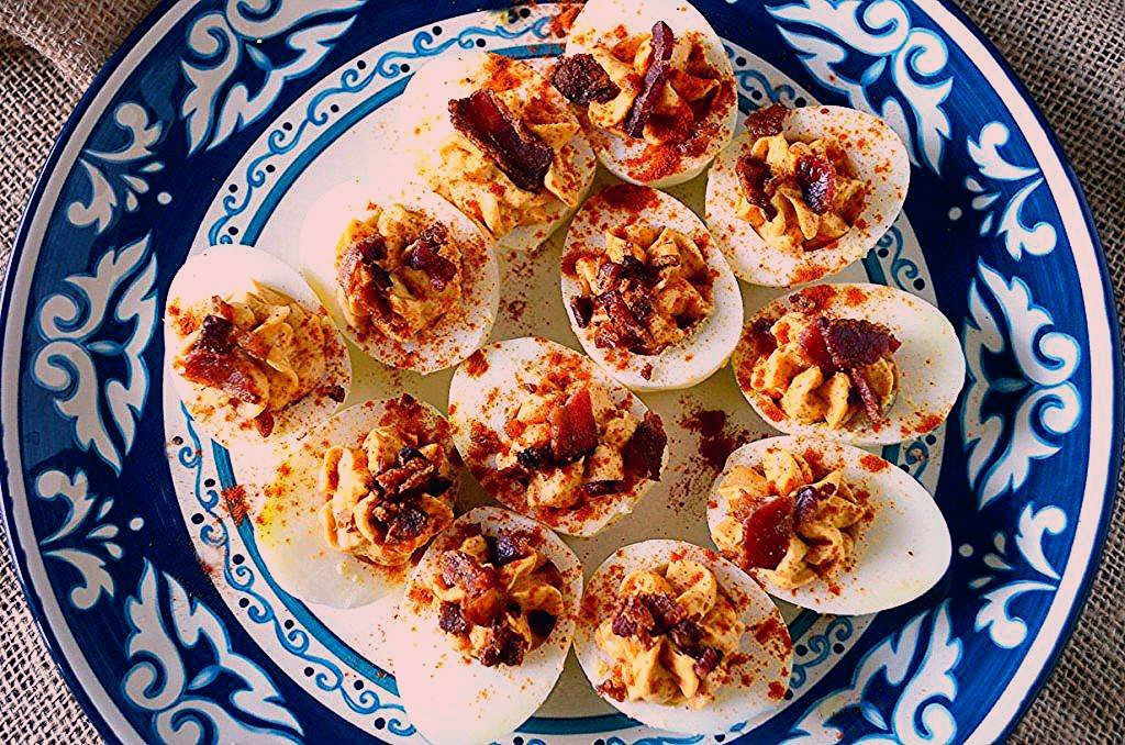 This is the BEST easy Bacon Sriracha Deviled Eggs recipe! The sriracha adds a spicy kick to a classic recipe that even rivals the Pioneer Woman! To add more heat, you could even top with jalapenos! #baconsrirachadeviledeggs #classicdeviledeggs #easterrecipes #easydeviledeggs #gogogogourmet #deviledeggs