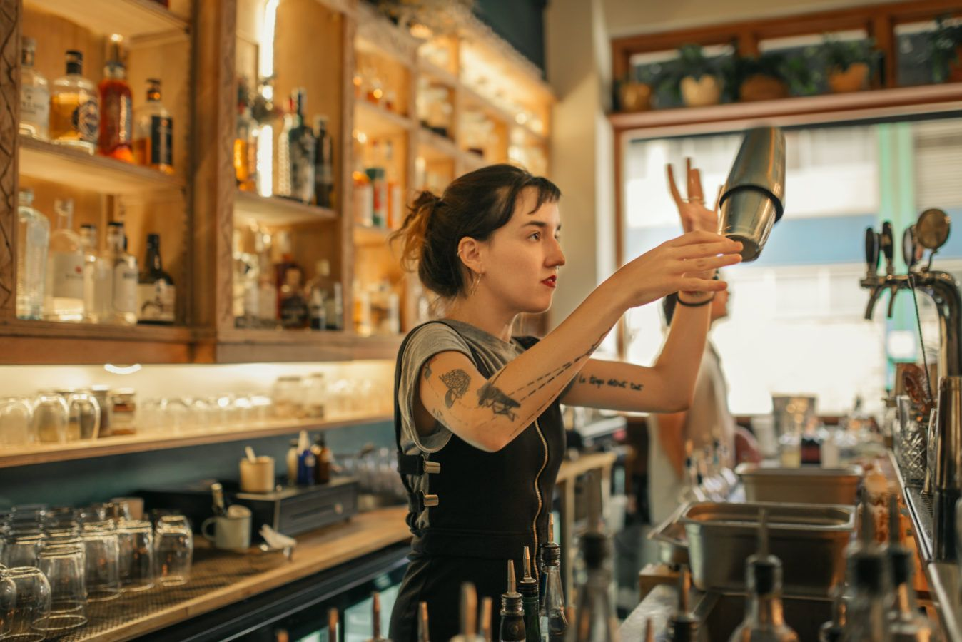 Young female bartender standing behind the counter of a