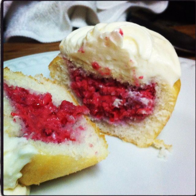 Insides of white cupcake with white chocolate raspberry filling and white chocolate icing