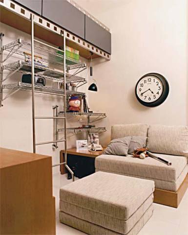 """P/ o cinéfilo, a arquiteta Ignez Ferraz criou armários horizontais de laminado grafite e portas basculantes, c/ perfil de aço perfurado imitando negativos de filmes"""". Acesso pela escada de metal apoiada nos quadrados vazados. A área foi dividida em 2 ambientes por um armário baixo, c/ TV giratória e fiação embutida. De um lado sofá e pufe se transformam em camas. O pufe se encaixa sob a mesa de cabeceira. Do outro, a bancada reúne computador, gaveteiros e mesa desdobrável p/ trabalhos em…"""