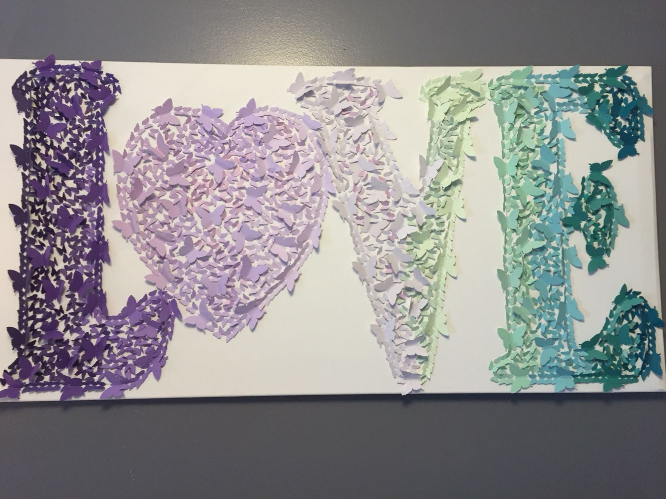 The ombré love picture I made for my daughter's room! Perfect for her purple and teal butterfly nursery. I used 2 different butterfly punches and some double sided scrap book paper, some canvas and glue, and lots and lots of time. I love I