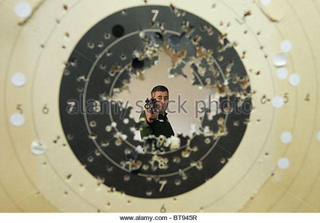 man-aiming-pistol-at-us-seen-through-shot-target-bt945r.jpg 640×446 pixels