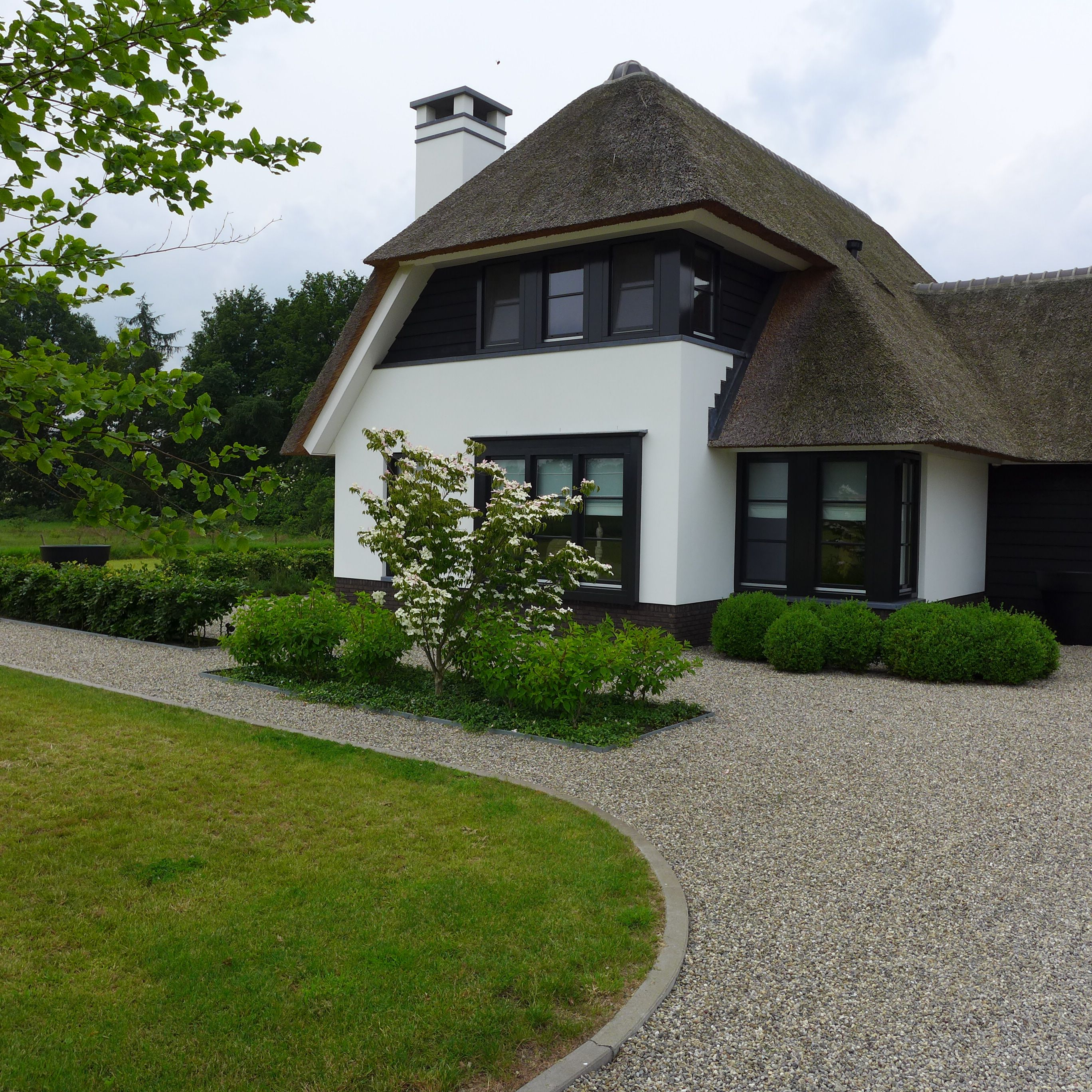 Moderne tuin. Rieten kap boerderij www.hendrikshoveniers.nl ...