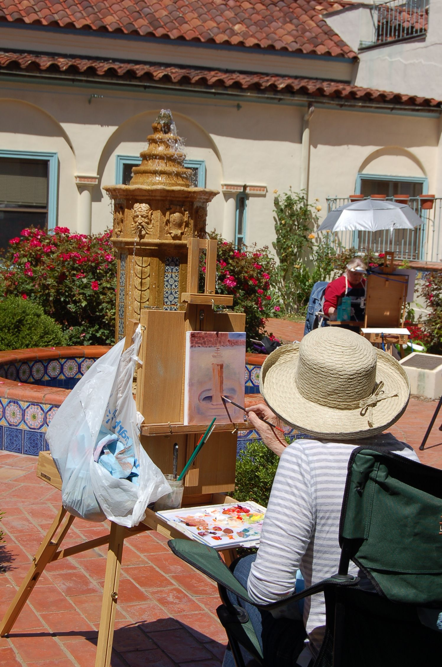 A painter captures the fountain in the La Quinta Mansion Rose Garden