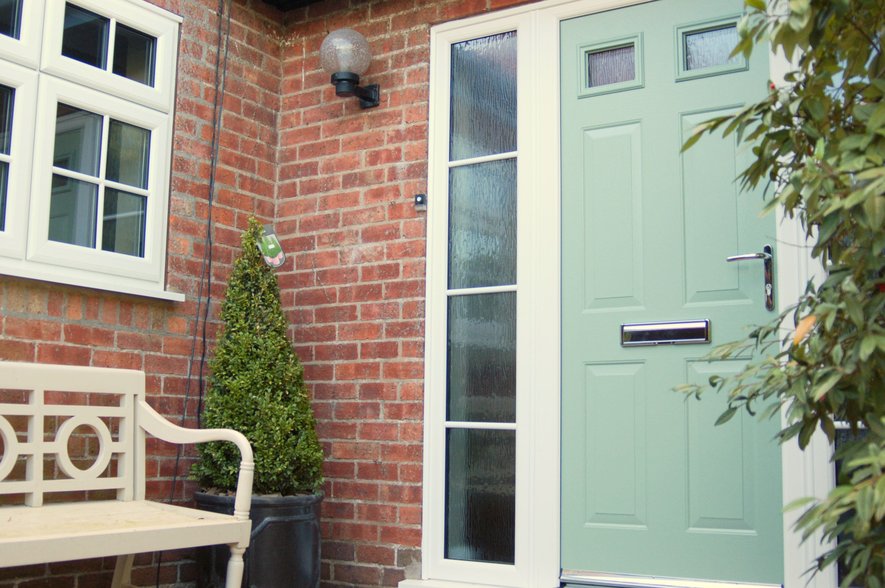 A light, sage green-coloured, double-glazed door with chrome trim ...