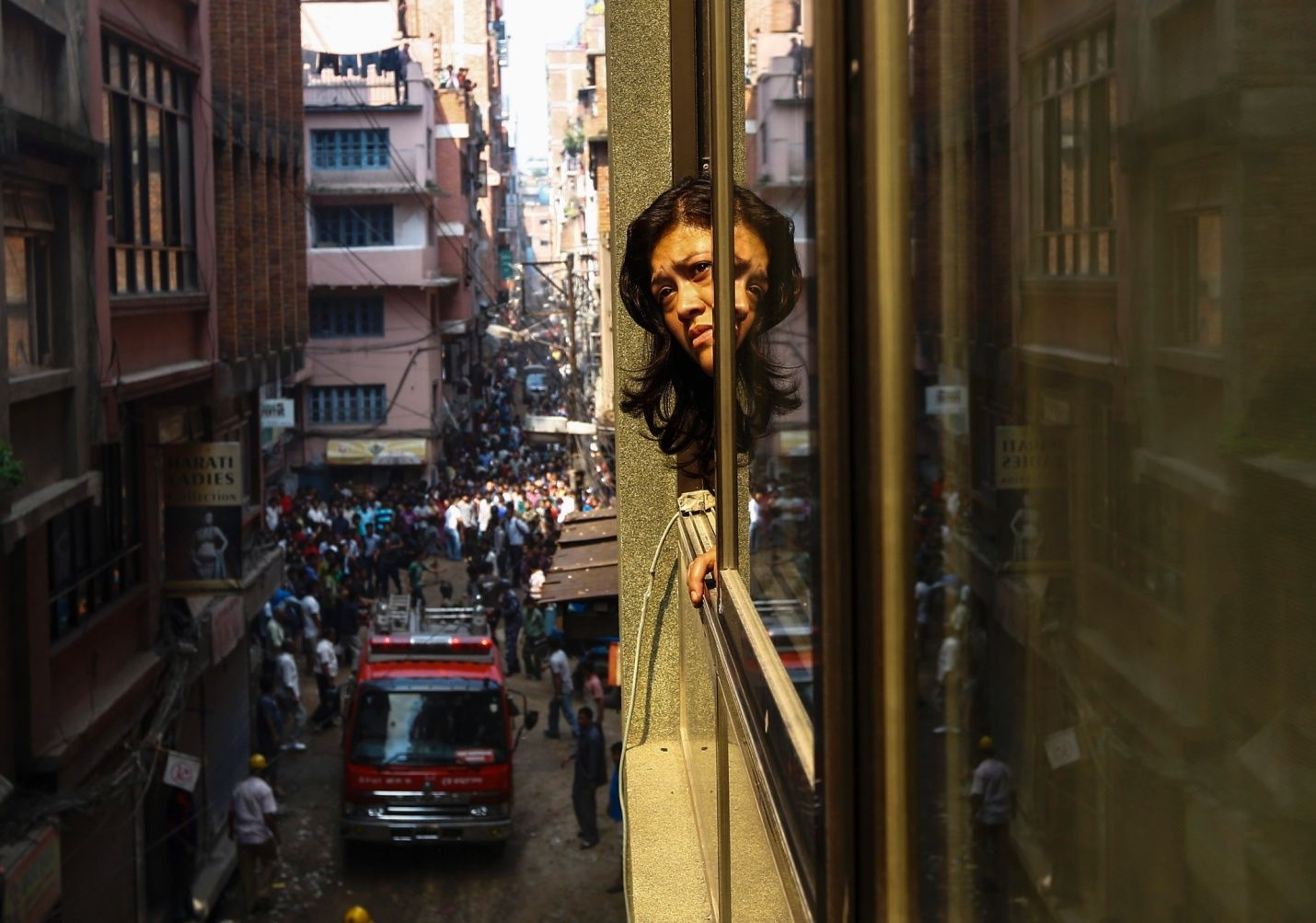 A woman watching firefighters from the window - Kathmandu, Nepal