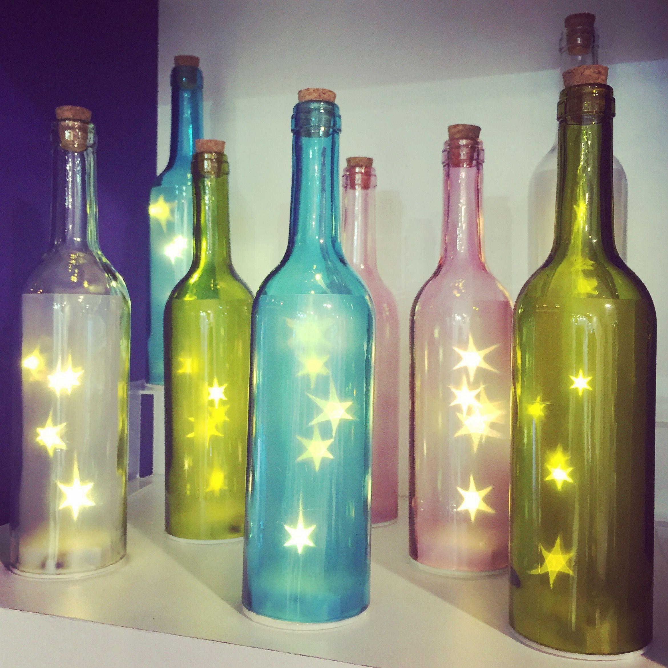 Krásné zátiší vytvořené barevnými láhvemi s LED osvětlením ...
