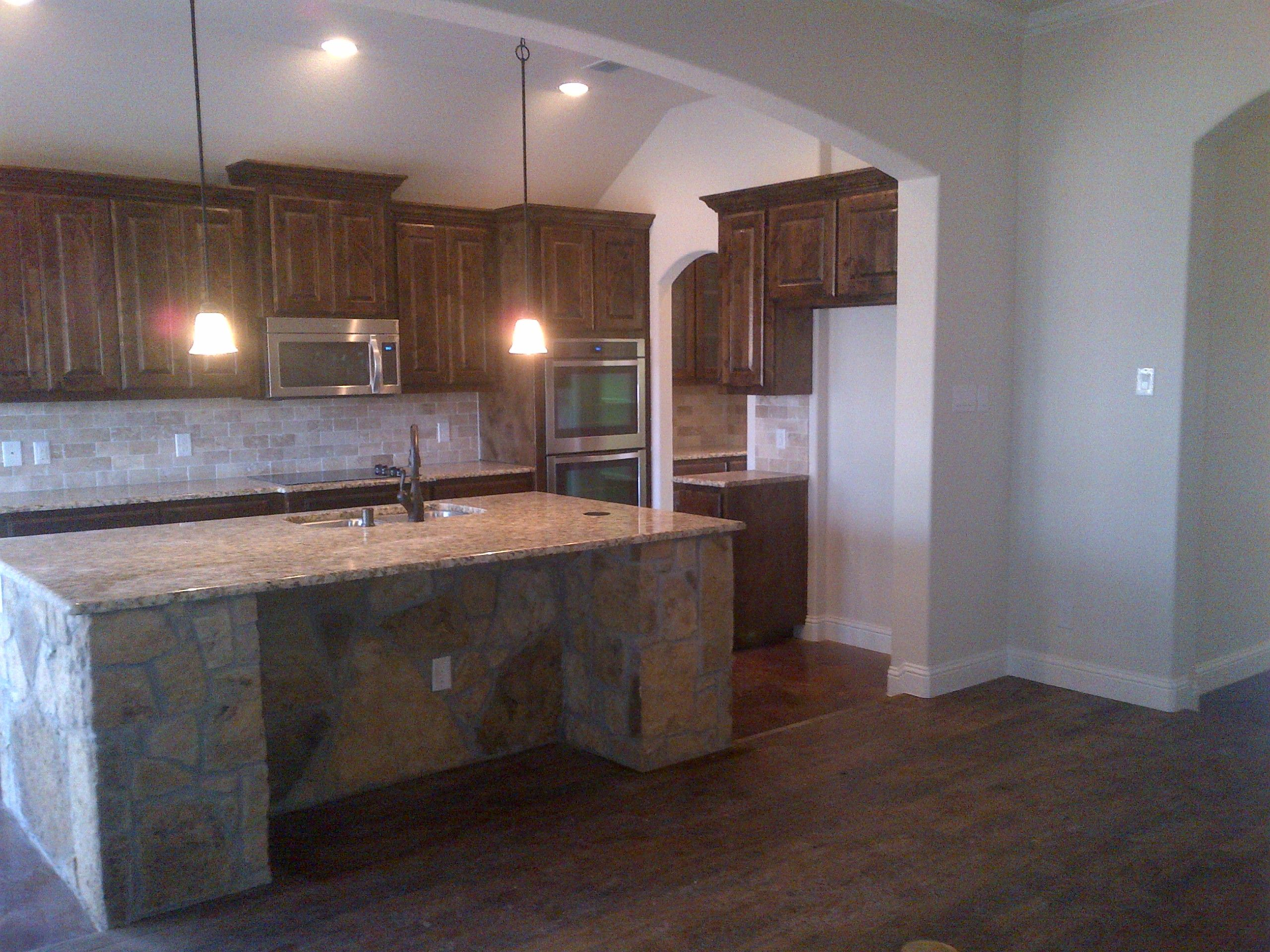 Dark walnut stained knotty alder cabinets travertine for Black stained cabinets