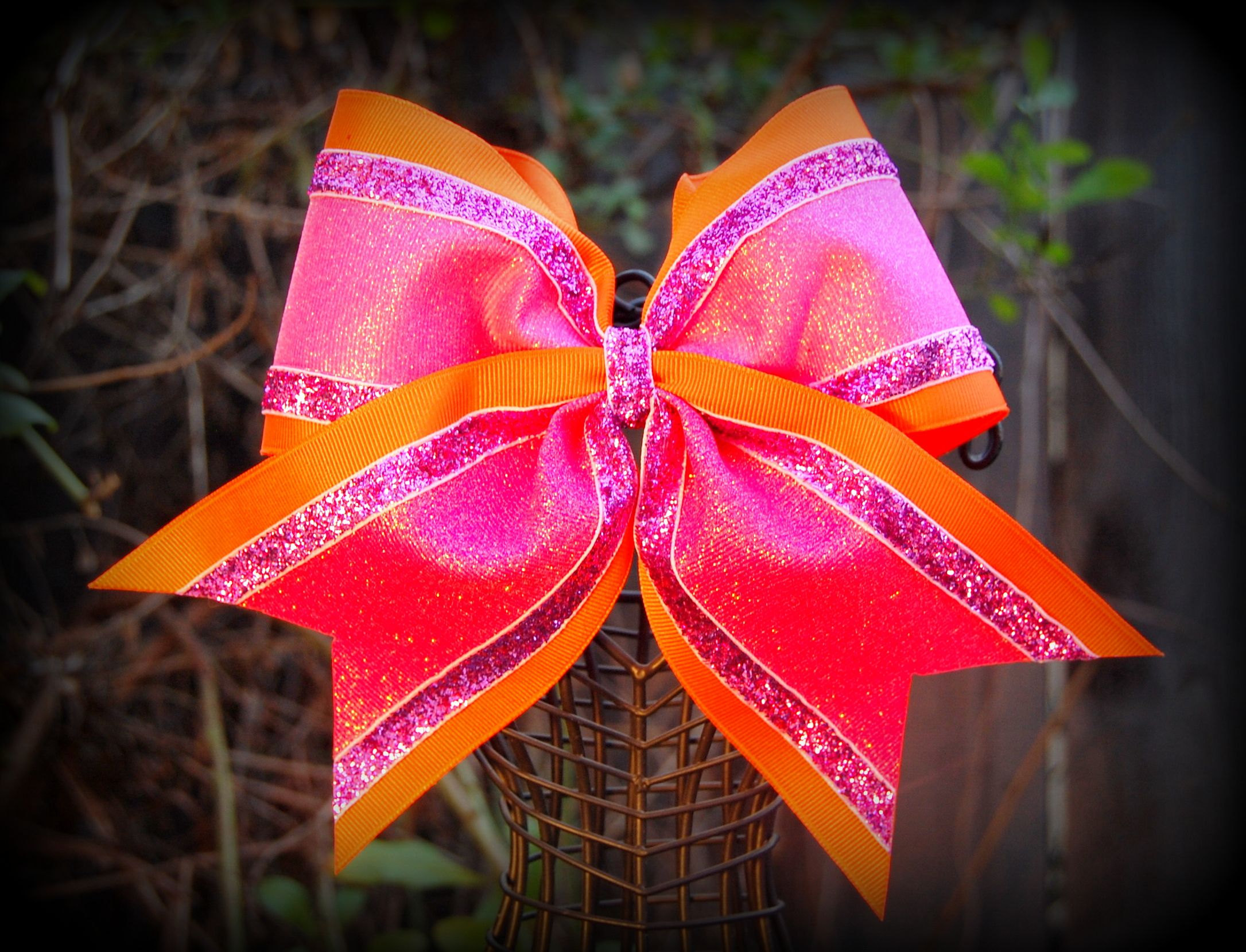 Hand crafted cheer bow in neon orange base hot pink glitter grosgrain center flanked by pink glitter velvet. See more on Facebook at  Ribbons and Bows Oh My  or our website at www.ribbonsandbowsohmy.net.   For custom design work email us at  ribbonsandbowsohmy.net@gmail.com