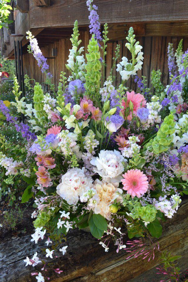 Pastel Ceremony Arrangement With Gerber Daisies Jasmine Snapdragons Delphinium Bells Of Ireland Alstroemeria Lisianthus Peonies And Dahlias Fleurish Fl