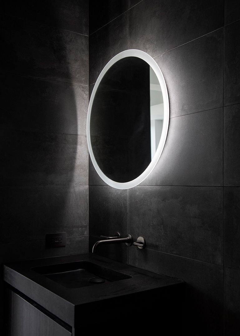 A graphite-finished Waterworks faucet sits below the mirror. | City ...