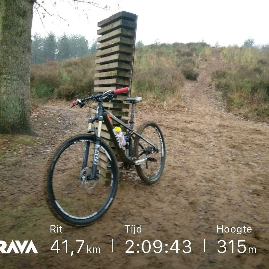 Mountainbike geplaatst tegen houten bord in de natuur