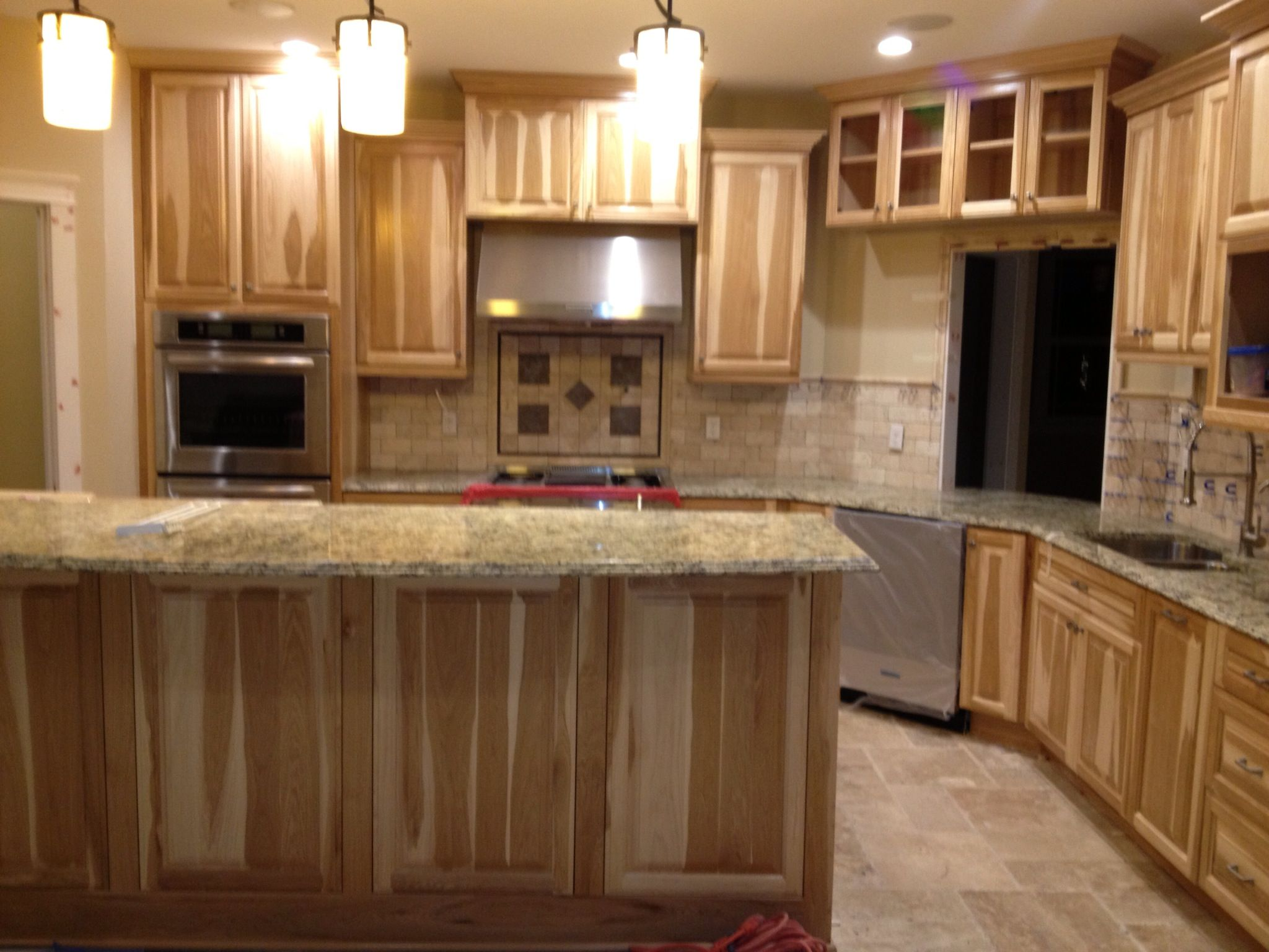 kitchen with hickory cabinets and travertine backsplash. with