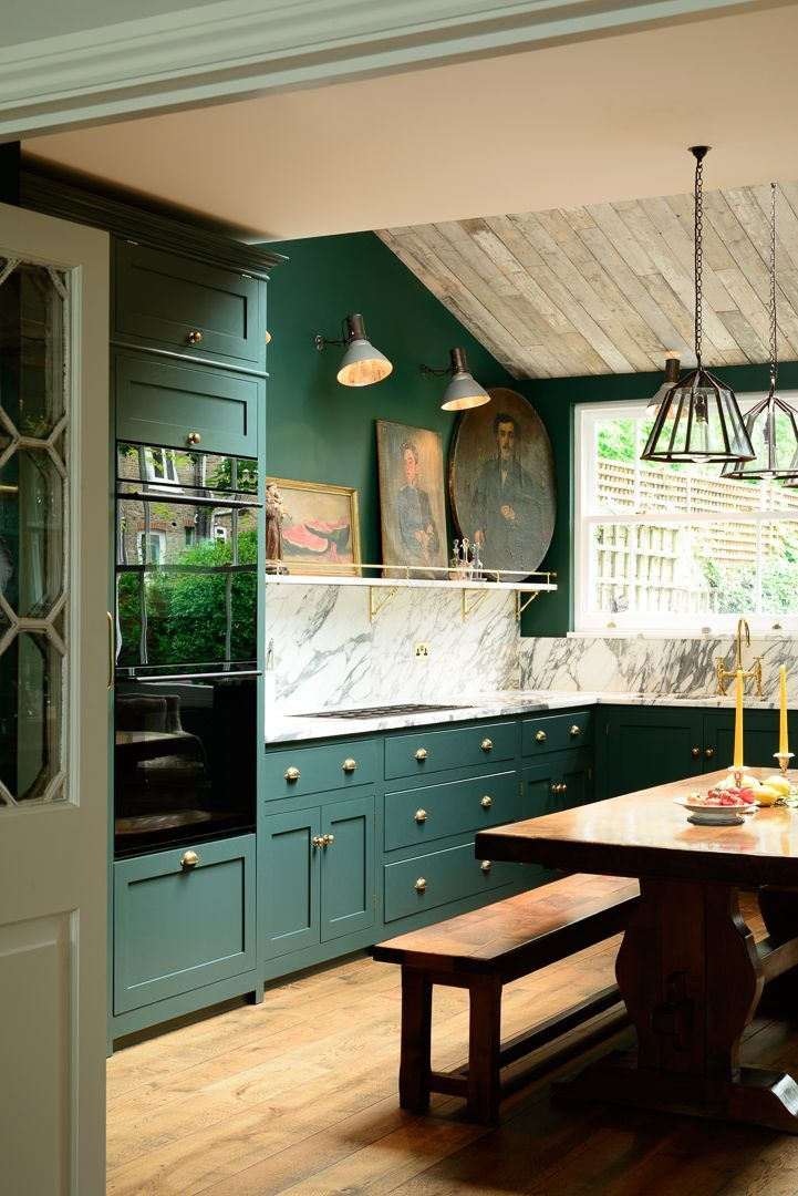 original kitchen design. Kitchen design  deep dark green cabinets and walls original wooden floorboards brass hardware lots of