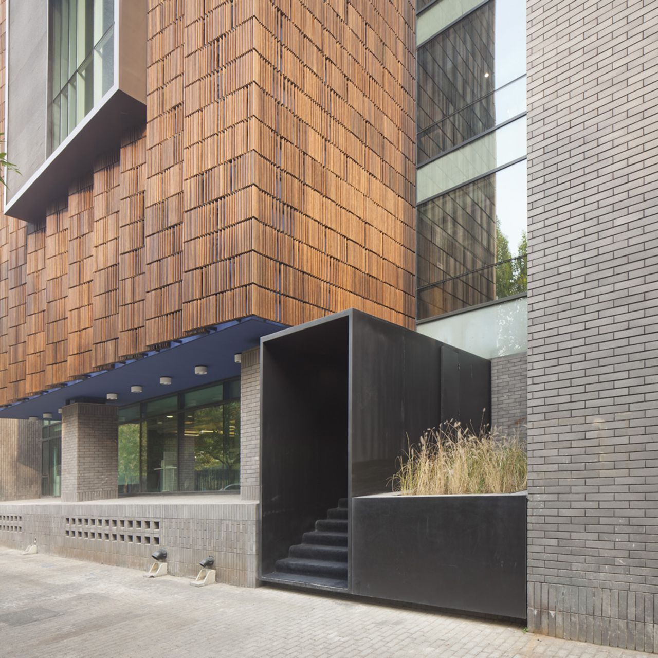 Brick wood glass stone facade with sheet metal entryway for Brick and stone house facades