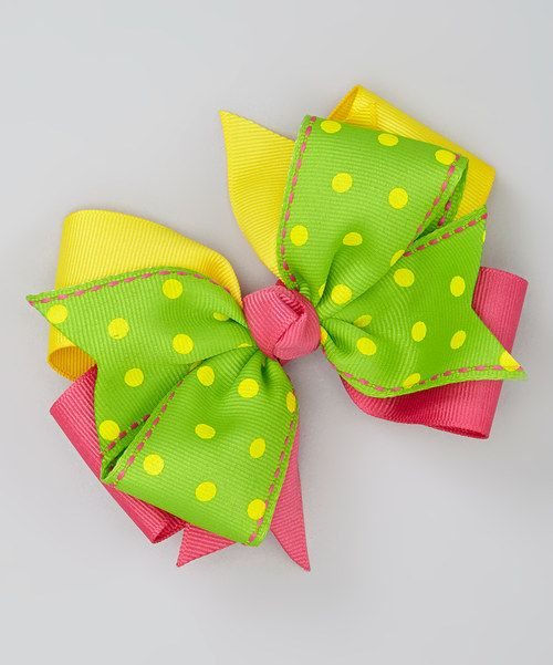 """Add sweet style to any lovely 'do with this playful polka dotted bow. Sporting a layered look and sturdy alligator clip base, it'll accent a little look with a touch of charm.4"""" W x 3.5"""" HPolyester / metalMade in the USA"""