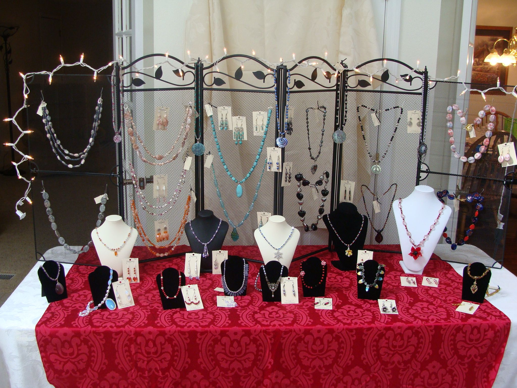 using a fireplace screen to hang necklaces or earrings to use as