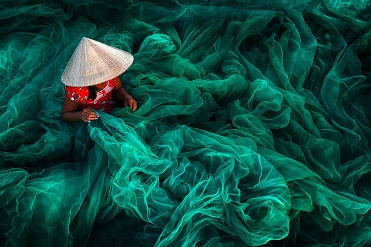 Danny Yen Sin Wong (Malaysia). Making fishing nets, Vietnam. Winner Open Color Category. This dreamy image captures a woman in the small fishing village of Phan Rang in southern Vietnam making a traditional fishing net. Handmade fishing nets are typically manufactured by women while the men are responsible for catching fish.