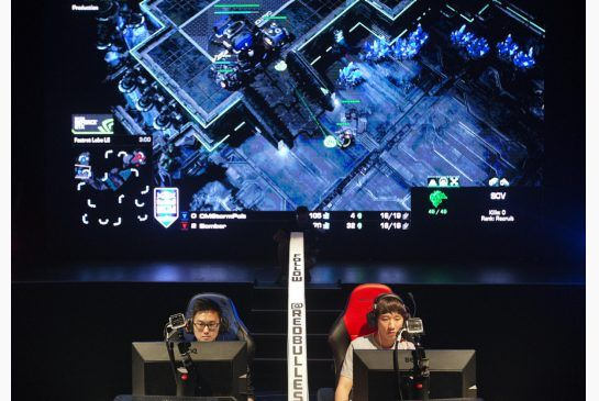 "In this July 13, 2014 file photo, Choi Seong Hun, left, who goes by the gaming name ""PoLt"" and Choi Ji Sung, known as ""Bomber,"" both of South Korea, are separated by a divider as they compete against each other in the finals of the Red Bull Battle Grounds ""StarCraft II"" video game tournament in Atlanta.   (AP Photo/David Goldman, File)"