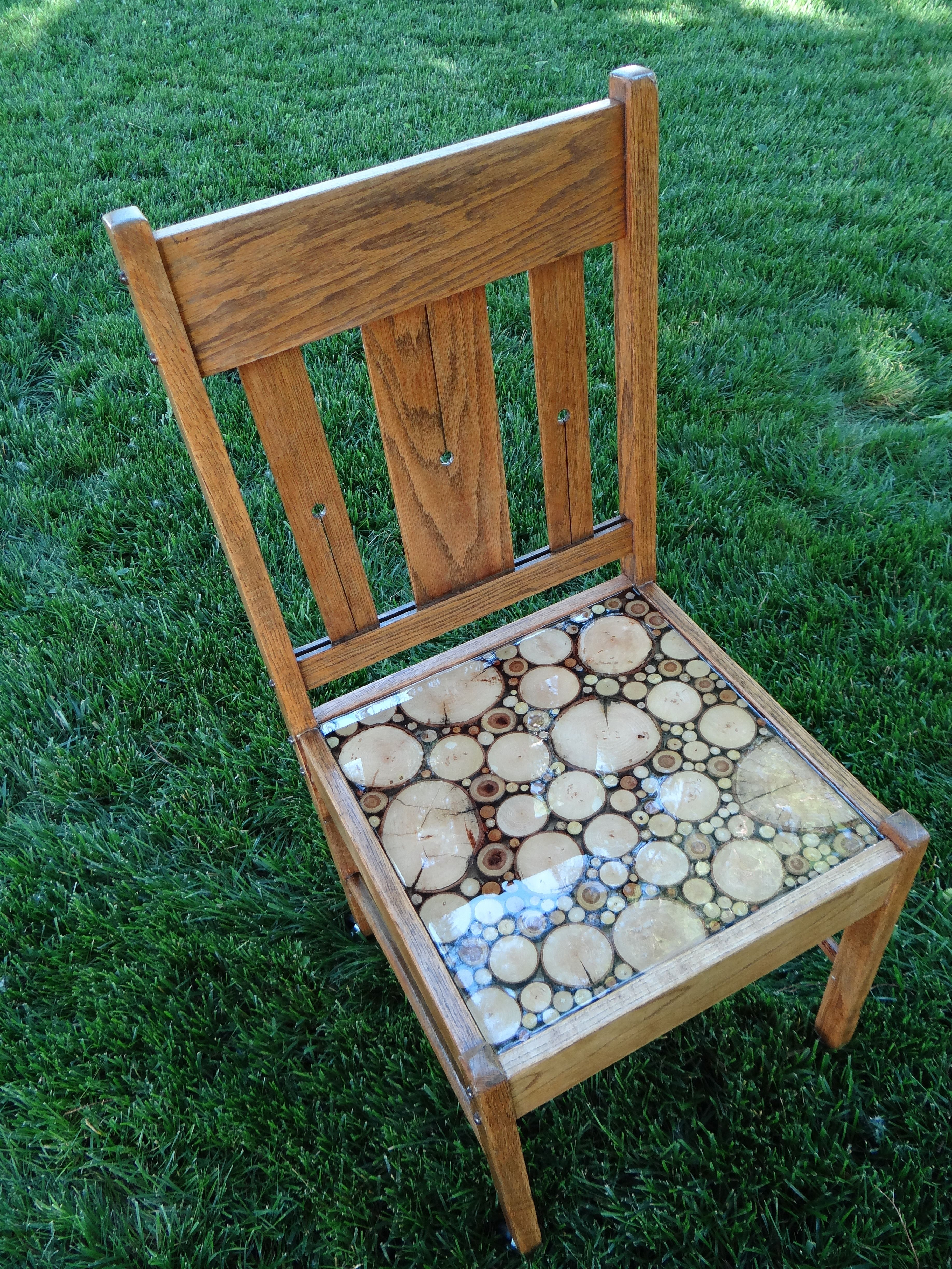"""""""Riding the Pines"""" An old chair that was missing it's seat was filled with 1/4"""" slices of wood and filled with resin.  4 wheels were added to raise it to the appropriate seating height"""