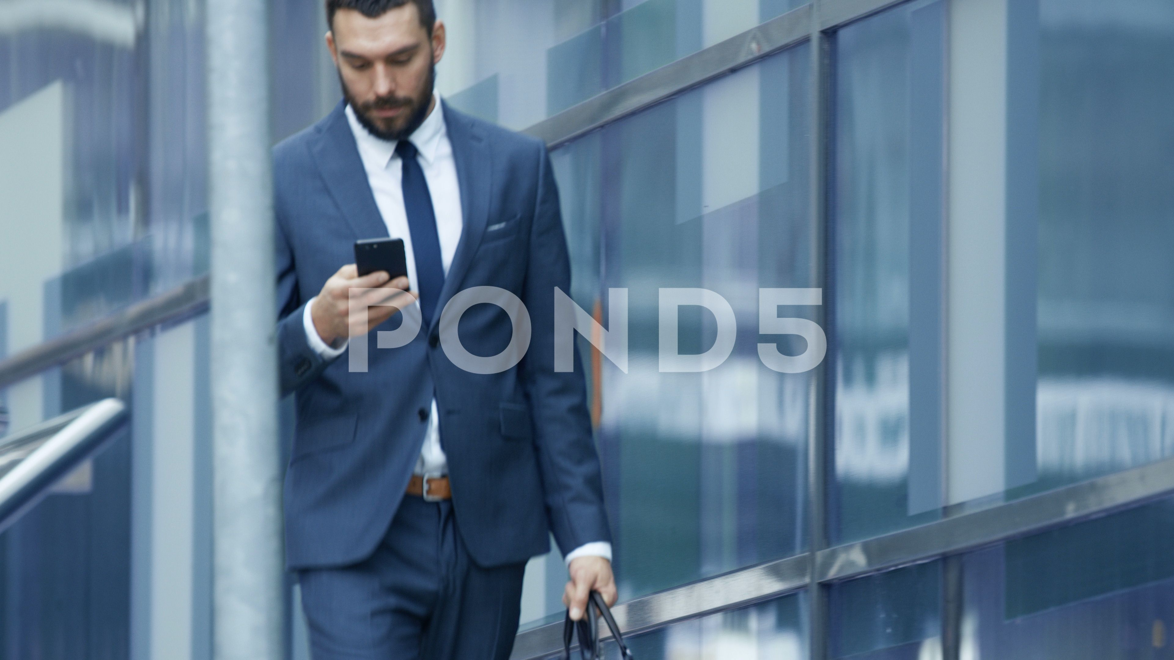 Successful Business Man Uses Smartphone While Walking On The Big