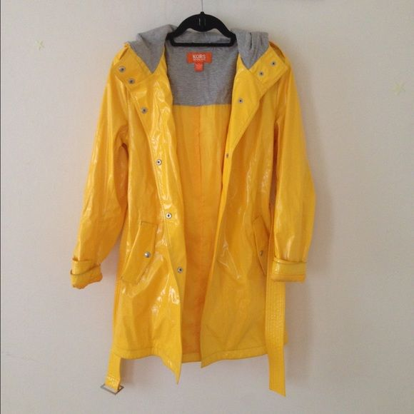 Michael Kors Belted Raincoat With the charm of childhood days spent jumping in rain puddles, this classic yellow jacket from Michael Kors is the rain slicker all grown up. With a belt, snap pockets, a hood and easy to fasten snap closures, it is as practice as it is stylish. This coat has a polyurethane shell, a yellow polyester lining and gray cotton sweatshirt material inside the hood for an extra sporty, casual touch. It is in great condition with two very small, barely noticeable marks…