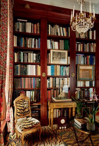 In a Paris apartment, a small space with outsize drama, the library is animated by tiger-stripe carpeting and a gilt-wood chair upholstered in a matching silk velvet by Le Manach from Pierre Frey; a rare 19th-century French clock nestles beneath an antique Roman console that displays a Louis XVI–period terra-cotta sculpture by Louis-Simon Boizot.  PHOTOGRAPHER: Pascal Chevallier HOMEOWNER: Sylvain Lévy-Alban & Charlie Garnett