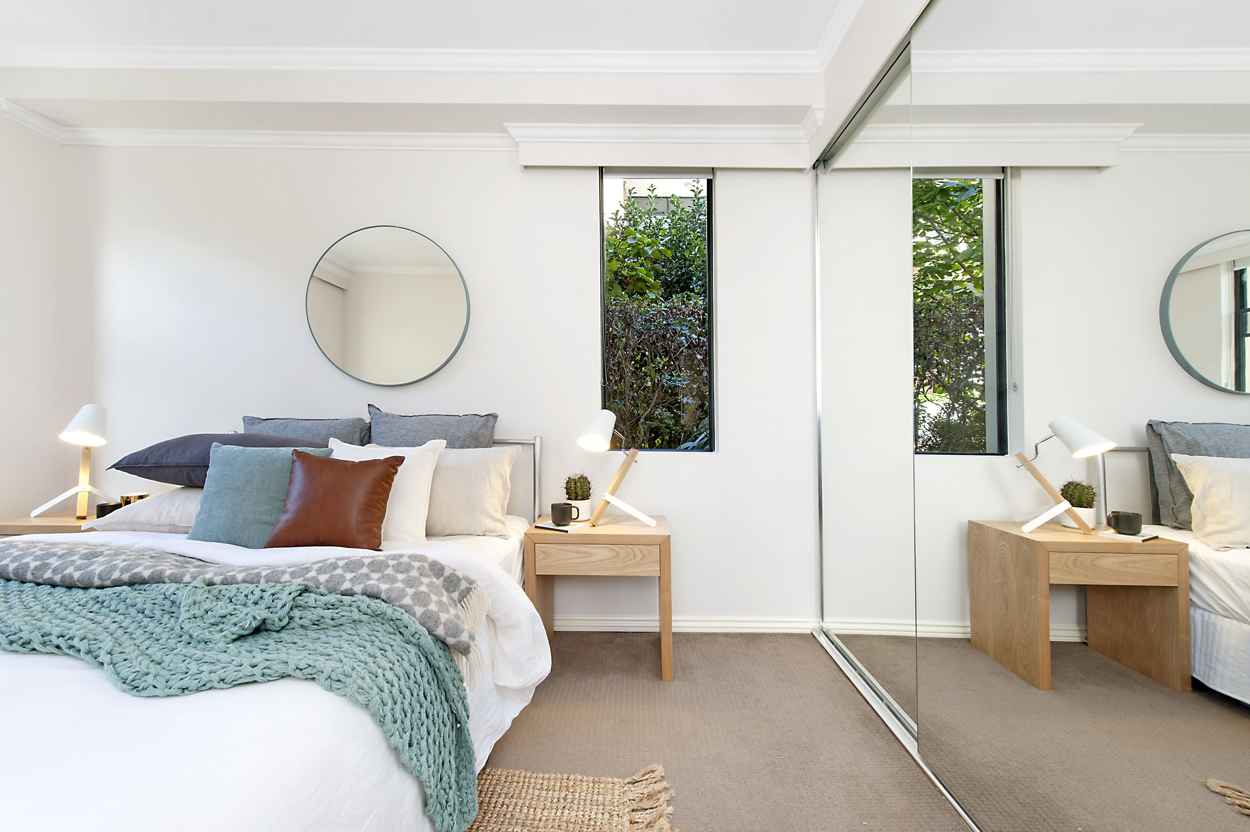 White bedroom with circular mirror over bed, lots of