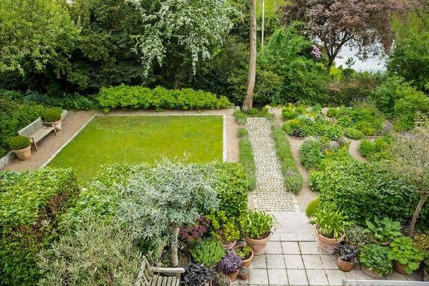 Græsplænens skarpe kanter og kvadratiske form er en fin kontrast til de vilde bede. Der er lige plads til picnictæppe og boulekugler.