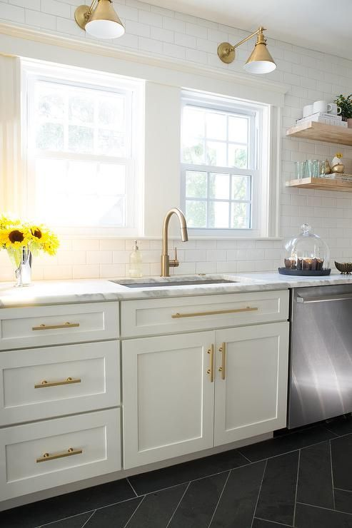 Photo of White and gold kitchen features white shaker cabinets adorned with brass pulls p…
