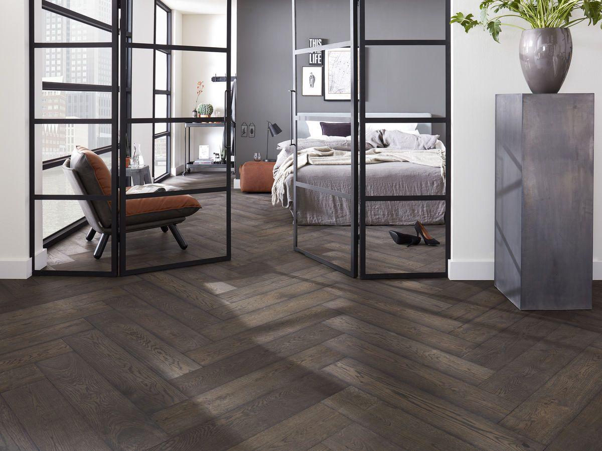 Donkere houten vloer gelegd als visgraat in een modern appartement